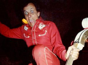 Ray Campi in red suit standing on his white double bass